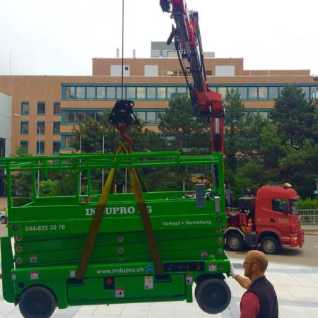 Eine Compact 10N wird am LKW-Kran zum Einsatzort gehoben